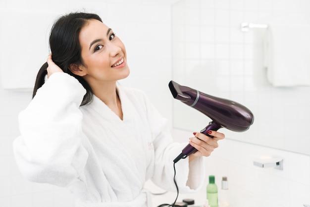 Милая счастливая оптимистичная молодая женщина в помещении дома в ванной комнате сушит волосы феном.