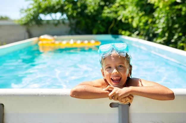 Милая счастливая маленькая девочка играет в бассейне в синей маске для дайвинга