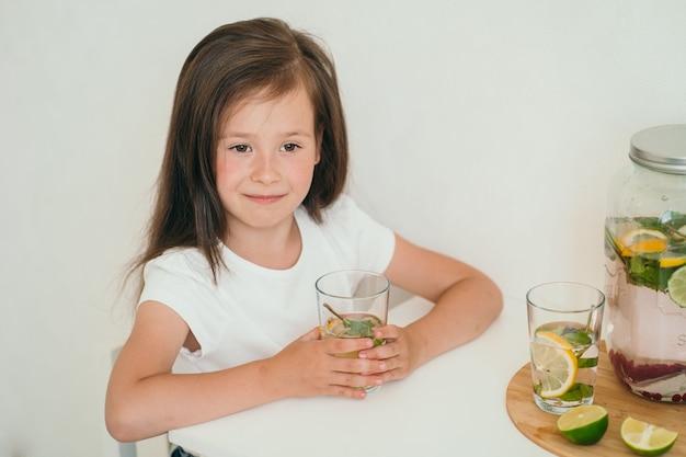 Симпатичный ребенок пьет домашний лимонад, полезный лимонад с лимоном и лаймом, летний прохладительный напиток ...