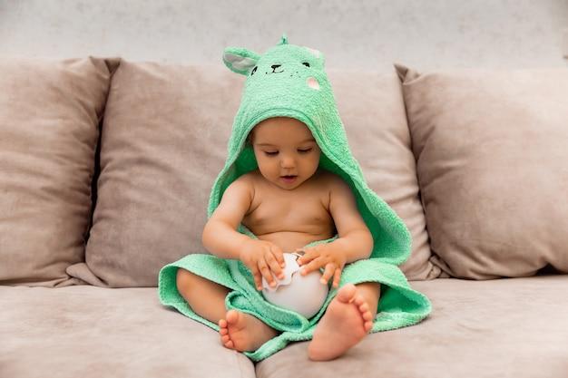 На кровати сидит милый малыш, завернутый в полотенце. ребенок в банном полотенце.