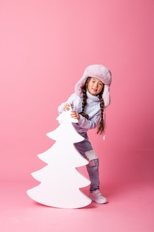 Милая маленькая азиатская девочка в зимней шапке стоит рядом с елкой на розовом фоне. зимняя концепция, место для текста