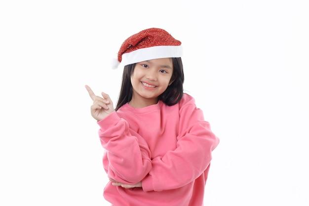 흰색에 가리키는 산타 클로스 모자를 쓰고 귀여운 아시아 소녀