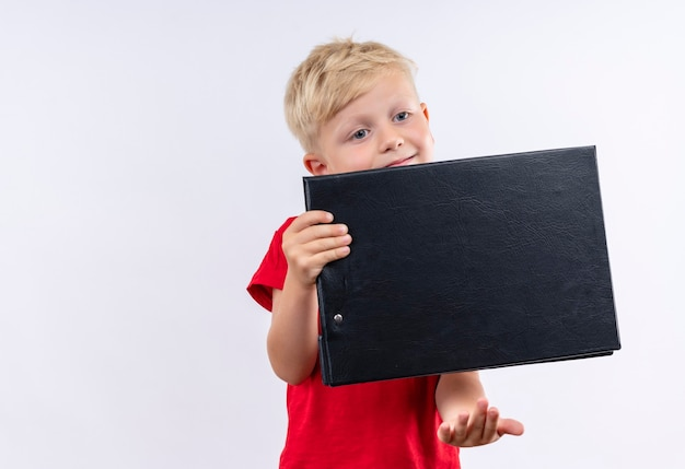 Милый маленький белокурый мальчик в красной футболке с пустой папкой на белой стене