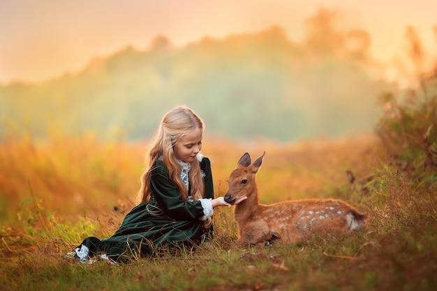 Милая маленькая блондинка в зеленом винтажном платье сидит рядом с маленьким пятнистым оленем вокруг желтых красивых осенних деревьев.