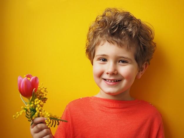 Милый маленький мальчик держит в руках букет тюльпанов и мимозы и улыбается