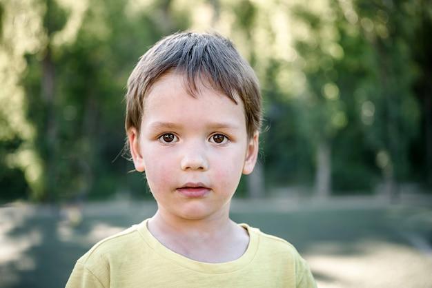 Милый маленький мальчик в желтой футболке на футбольном поле