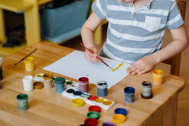 Милый маленький мальчик играет и рисует в своей комнате. отдых и развлечения. оставайся дома.