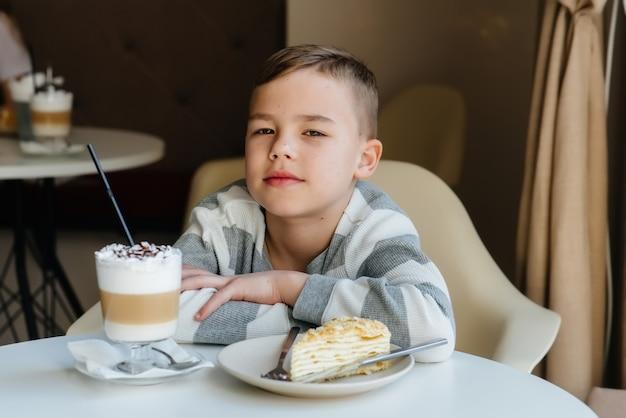 귀여운 어린 소년이 카페에 앉아 케이크와 코코아 클로즈업을보고 있습니다. 식이 요법과 적절한 영양.