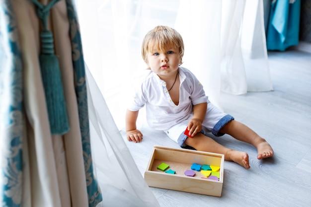 귀여운 어린 소년이 집에서 바닥에 앉아 나무로 만든 여러 가지 교육 장난감에서 놀고 있습니다.
