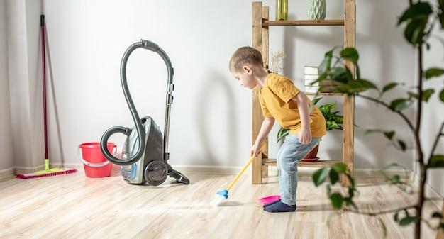 귀여운 소년이 빗자루로 바닥에서 쓰레받기까지 쓰레기를 쓸고 있습니다. 아이는 부모가 집을 청소하는 것을 돕습니다.