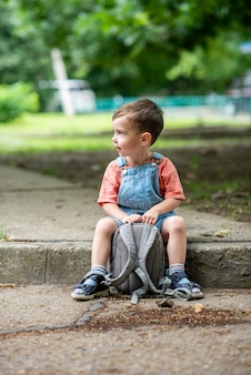 Милый маленький мальчик смотрит в камеру, держит в руках сумку. одет в джинсовый комбинезон эрл.