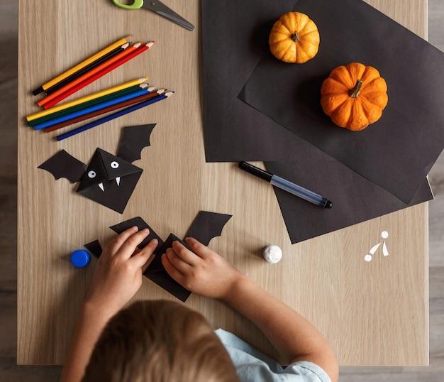 かわいい男の子が黒い紙でハロウィンのバットを作りました。子供の手仕事。