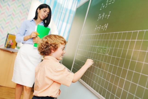 Симпатичный маленький мальчик-школьник с вьющимися волосами пишет мелом на доске и решает математику ...