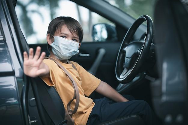 전염병 동안 방과 후 차에서 보호용 안면 마스크를 쓴 귀여운 소년
