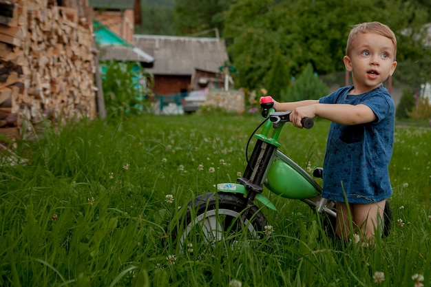 Милый маленький мальчик с велосипедом возле дома, детский спорт, активная семья на улице.