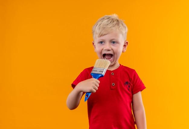 Симпатичный маленький мальчик со светлыми волосами и голубыми глазами в красной футболке, держащий синюю кисть рядом со ртом, глядя сбоку на желтой стене