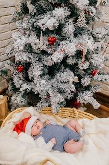 파란색 잠옷에 귀여운 작은 아이와 빨간 새해 모자는 크리스마스 트리 근처에 짠 바구니에 놓여 있습니다