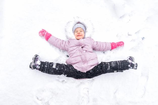 Милая девочка 4 лет в розовом пуховике лежит в сугробе на шпагате и радуется снегу. зимние развлечения