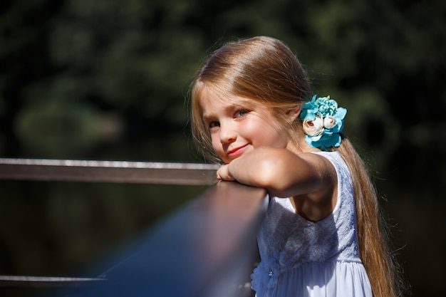 Милая маленькая девочка 6-7 лет с длинными светлыми волосами, она одета в летнее балетное платье, она стоит на фоне реки.