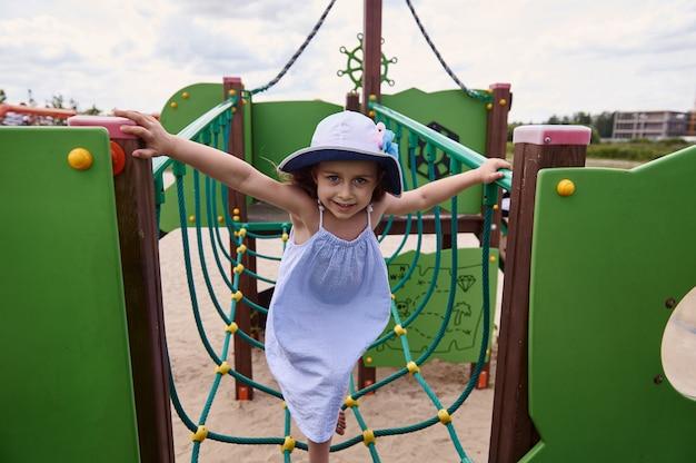 Милая маленькая девочка лазит по канатам на детской площадке летнего детского лагеря. активен во время летних школьных каникул