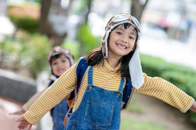 모자를 쓰고 조종사의 안경을 쓴 귀여운 소녀. 조종사가 꿈인 아이.