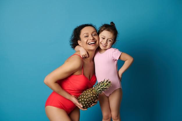 Милая маленькая девочка обнимает маму с ананасом на руках, обе в купальниках. счастливый день матери и летние концепции