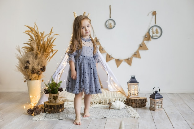 아름다운 드레스를 입은 귀여운 소녀가 집에서 wigwam에서 활약합니다. 새해 장식.