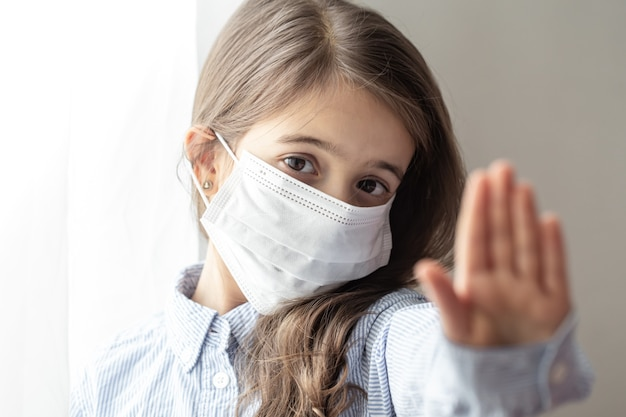 Милая маленькая девочка в одноразовой защитной маске от коронавируса