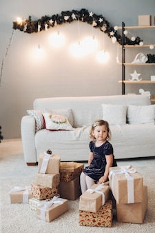 ドレスを着たかわいい女の子がクリスマスプレゼントの箱に囲まれて座って、それらを開けたいと思っています