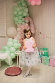 Милая маленькая девочка в пышном платье стоит с подарком в новогодних украшениях