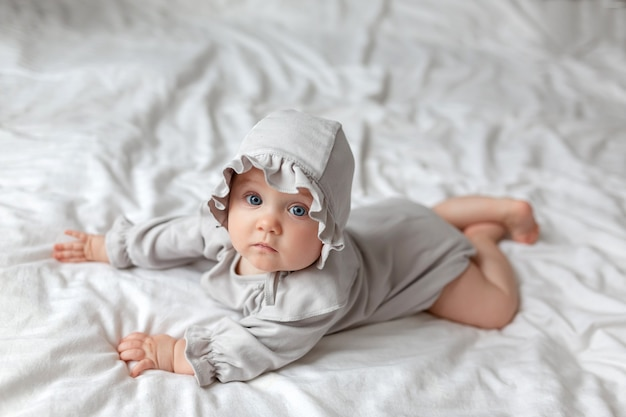 Милая маленькая девочка в легком красивом легком боди и кепке на кровати дома