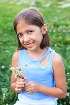 여름날 풀밭에 있는 귀여운 소녀가 여름 꽃 한 다발을 손에 들고 카메라를 바라보며 미소를 짓고 있습니다.
