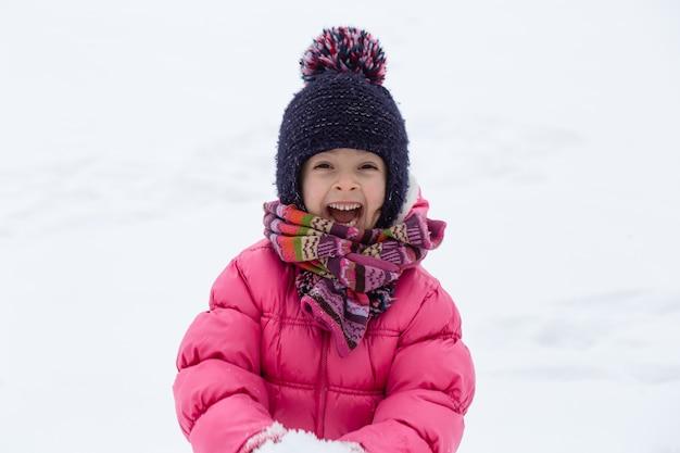 ピンクのジャケットと帽子をかぶったかわいい女の子が雪の中で遊んでいます。冬の子供向けエンターテインメントのコンセプト。