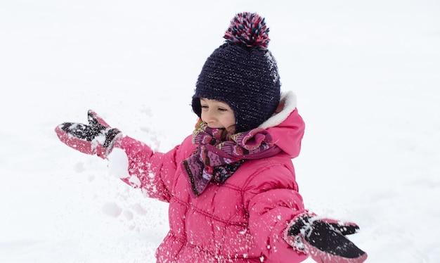 분홍색 재킷과 모자를 입은 귀여운 소녀가 눈 속에서 놀고 있습니다. 겨울 어린이 엔터테인먼트 개념.