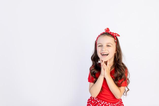 孤立した白地に赤いドレスを着たかわいい女の子が頬に手を組んだ。テキストのためのスペース。小さな女の子が誕生日、休日の概念と販売を祝う