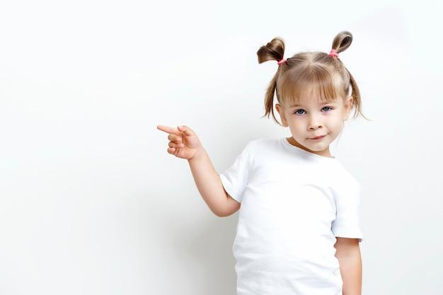 白いtシャツを着たかわいい女の子が彼女の近くの空きスペースを指しています。 Premium写真