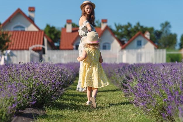 Милая маленькая девочка в соломенной шляпе и желтом платье бежит домой к своей красивой маме в летнем платье