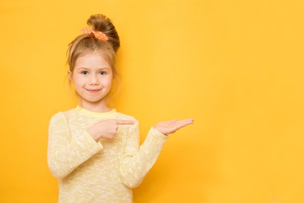 귀여운 소녀는 무언가에 손가락을 가리키는 관심에 끌립니다.