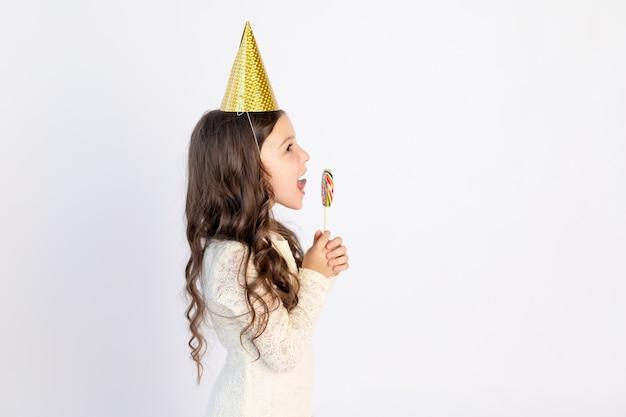 かわいい女の子は、孤立した白地のお祝い帽子で大きなロリポップを食べています。テキストのためのスペース。小さな女の子が誕生日、休日の概念を祝う