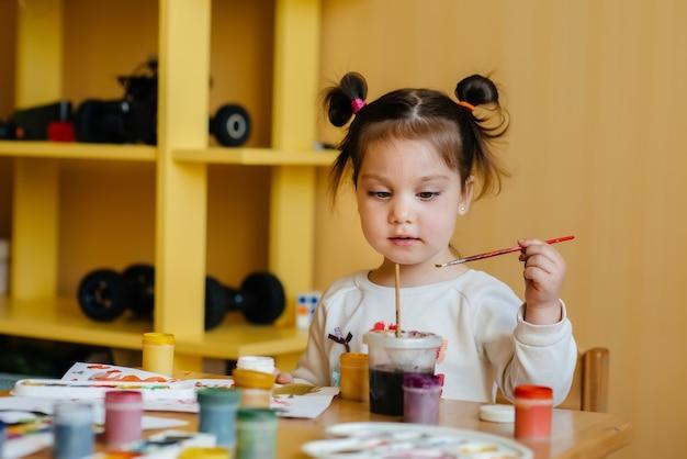 Милая маленькая девочка играет и рисует в своей комнате. отдых и развлечения.