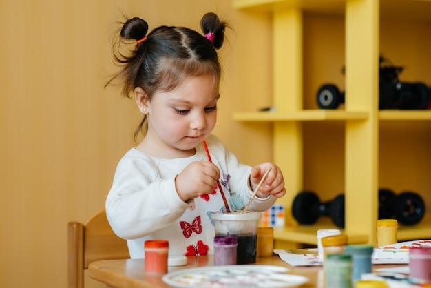 귀여운 소녀가 그녀의 방에서 놀고 그림을 그리고 있습니다. 레크리에이션 및 엔터테인먼트.