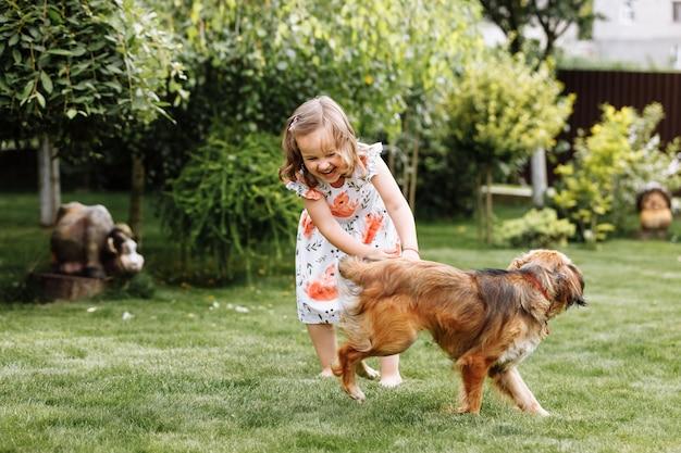 Милая маленькая девочка играет со своей собакой на улице дома на траве.