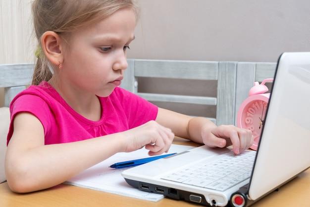 Милая маленькая девочка сидит за столом и печатает домашнее задание на ноутбуке, чтобы отправить учителю на проверку. концепция обучения, дистанционное обучение, самообразование, урок видеоконференцсвязи с наставником