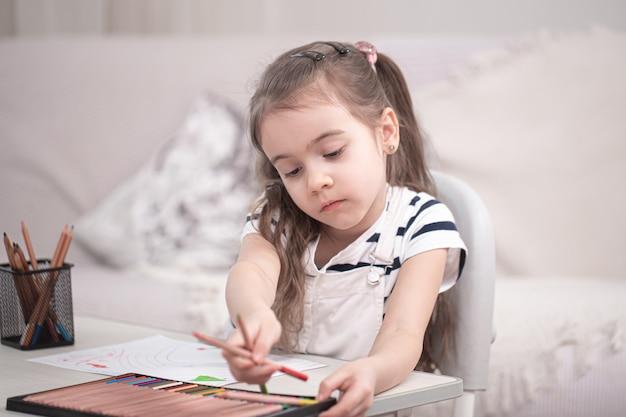귀여운 소녀가 테이블에 앉아 숙제를하고 있습니다. 홈 스쿨링 및 교육 개념.