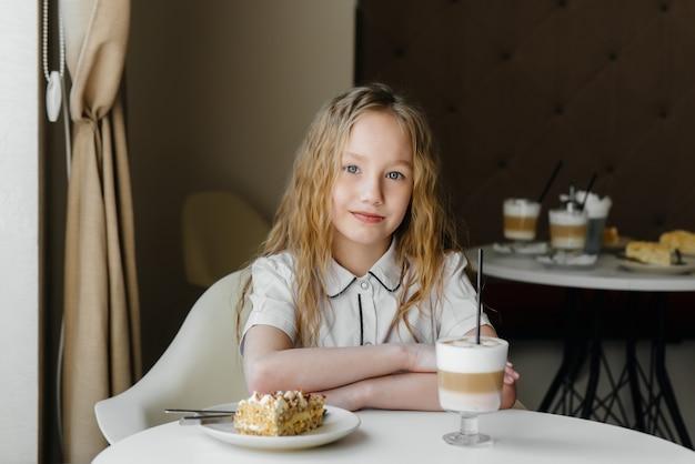 귀여운 소녀는 카페에 앉아 케이크와 코코아 클로즈업을보고. 다이어트와 적절한 영양 섭취.