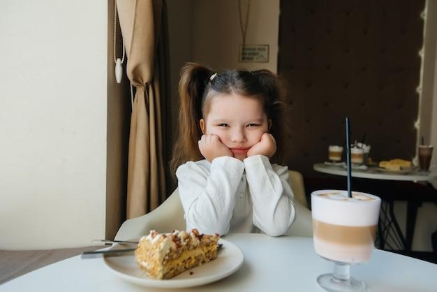 Милая маленькая девочка сидит в кафе и смотрит на торт и какао крупным планом. диета и правильное питание.