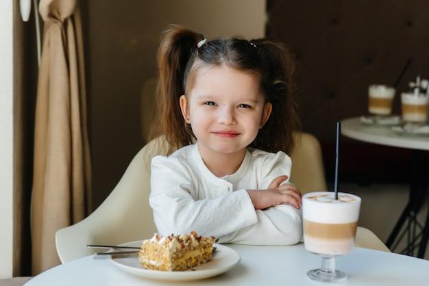 かわいい女の子がカフェに座って、ケーキとココアのクローズアップを見ています。
