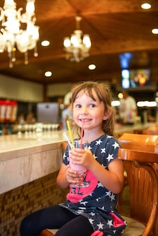 Милая маленькая девочка сидит в кафе за прилавком и пьет коктейль. все включено, море и летний отдых.