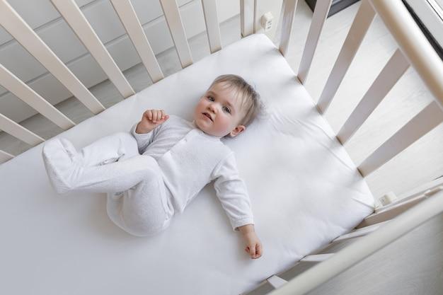 Милая маленькая девочка улыбается, лежа в детской кровати с белыми простынями.