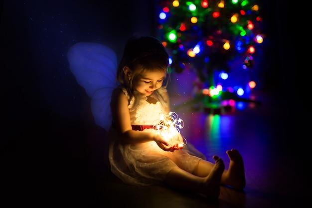 かわいい女の子がクリスマスの花輪に魔法の休日を照らします